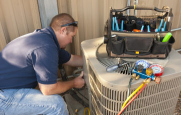 HVAC technician providing air conditioning services to an existing unit.